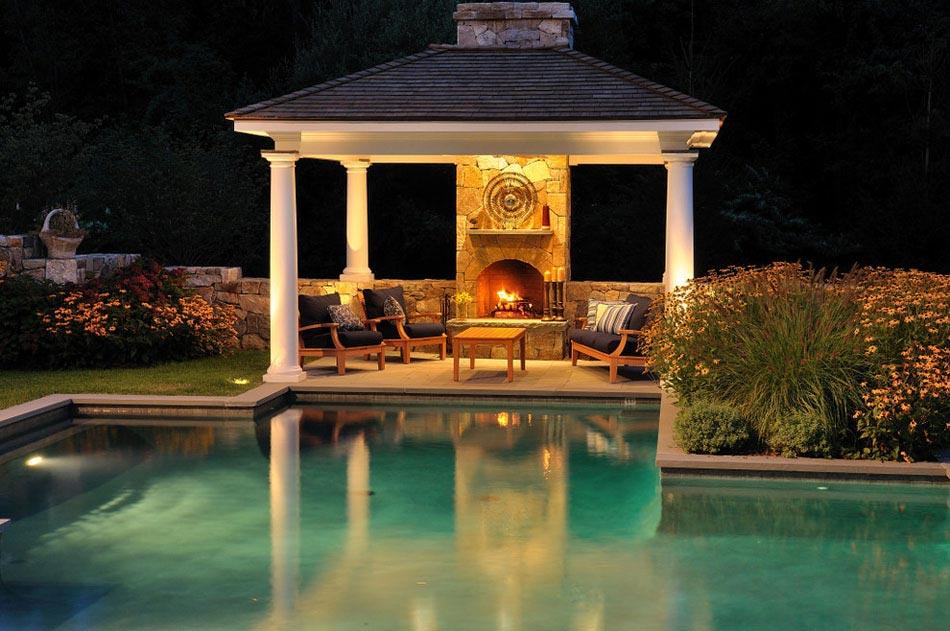Une cheminée extérieure à côté d'une piscine design ...