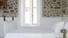 Chambre rustique au plafond en bois et mur en pierres