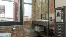 Murs en briques brut douche et baignoire chics